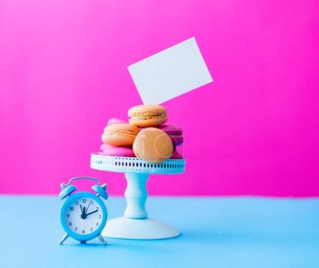 Photo for Macaroons on stand with vintage alarm clock on bright pink background - Royalty Free Image