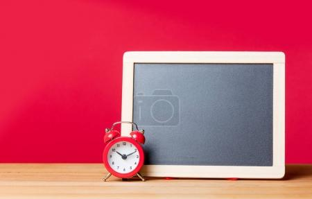 alarm clock and blank blackboard