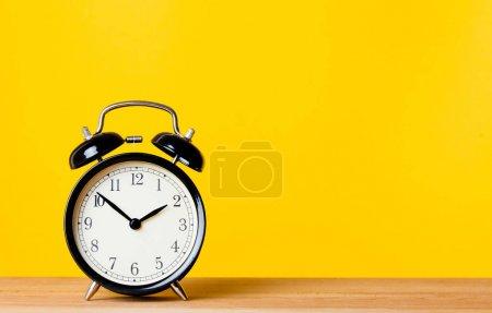 Photo pour Noir petit réveil sur la table en bois sur un fond jaune avec fond - image libre de droit