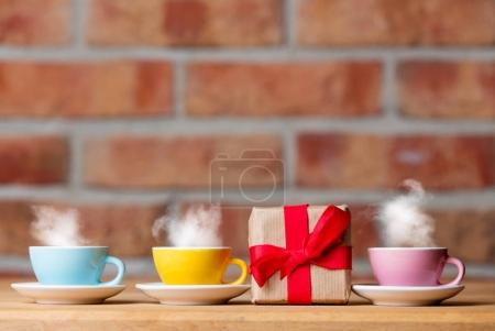 cups of hot tea and gift box
