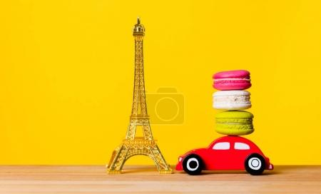 Photo for Eiffel tower, toy car carrying delicious macarons on wooden table over bright yellow background - Royalty Free Image