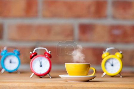 cup of hot tea and alarm clocks