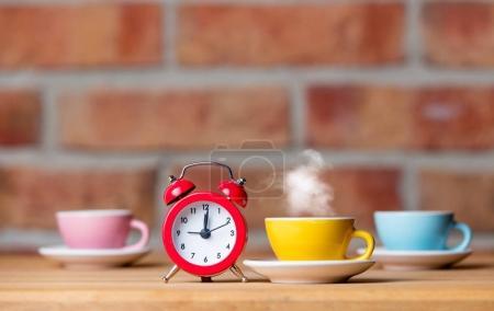 cups of hot tea and alarm clock