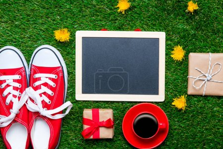 Photo for Red sporty gumshoes, gift boxes, coffee cup and blank blackboard on green grass background with yellow flowers - Royalty Free Image