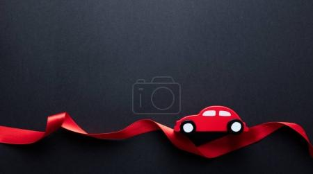 toy car on red ribbon