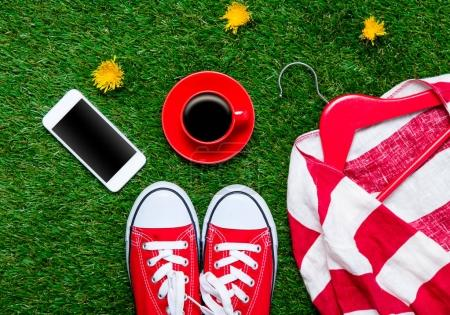 Photo for Red sporty gumshoes, coffee cup, smartphone and clothes on hanger on green grass background with yellow flowers - Royalty Free Image
