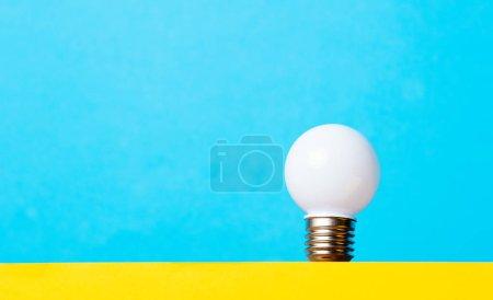 Photo pour Petite ampoule blanche sur fond bleu, idée et concept de créativité - image libre de droit