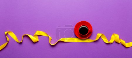 cup of coffee with yellow ribbon
