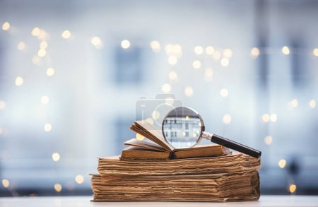 Old books and magnifier on fairy lights
