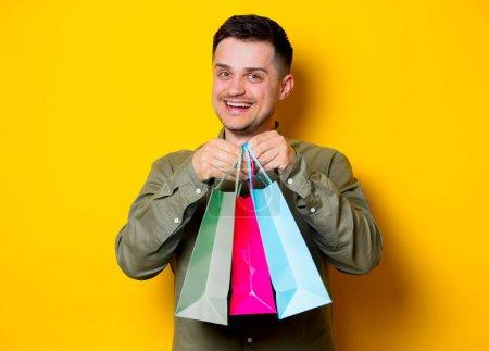 Photo pour Jeune homme heureux avec des sacs à provisions colorés sur fond jaune - image libre de droit