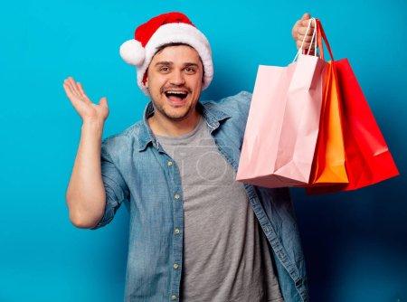 Photo pour Beau homme en chapeau de Noël avec des sacs à provisions sur fond bleu - image libre de droit