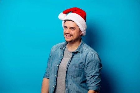 Photo pour Beau homme en chapeau de Noël sur fond bleu - image libre de droit