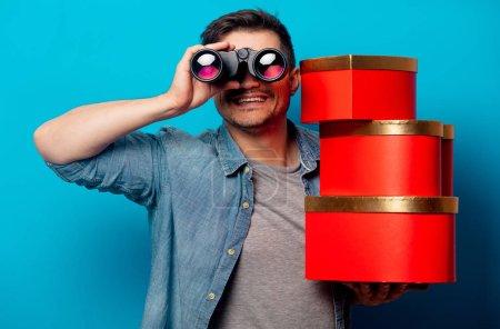 Photo pour Homme surpris avec jumelles et cadeaux rouges sur fond bleu - image libre de droit