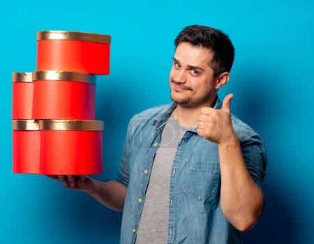 Photo pour Bel homme avec des cadeaux rouges sur fond bleu - image libre de droit