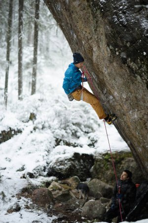 Extreme winter sport climbing. Young male rock climber on a rock wall. Snowy forest on the background,