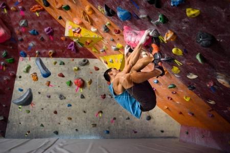 Photo pour Exercice d'entraînement. Homme sportif sur un mur d'escalade, sports d'intérieur. bel homme avec forme et corps musclé . - image libre de droit