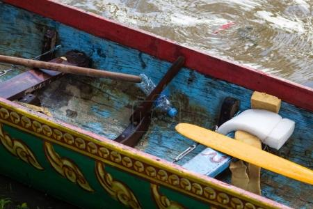 Interior detail of wooden racing boat after a traditional racing event in Cambodia, revealing paddles, painted detail, and water bottles