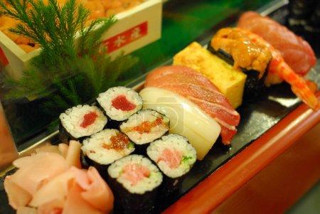 Photo pour Délicieux sushis sur planche de bois au marché aux poissons Tsukiji japonais - image libre de droit