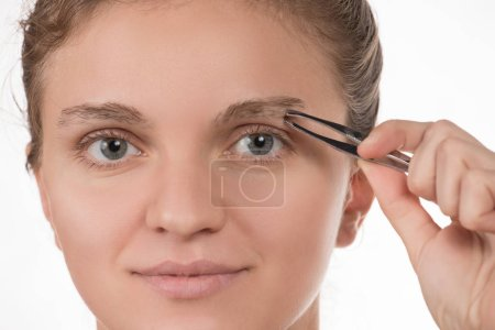 Young girl pulls out her eyebrows with tweezers metal on a white