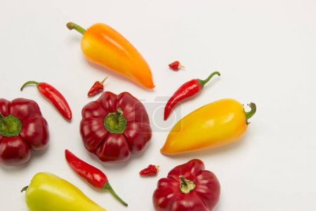 Foto de Varios dulce madura hermosa y caliente pimientas de rojo y naranja sobre un fondo blanco - Imagen libre de derechos