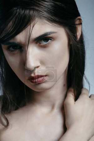 Foto de Retrato de una chica morena con el pelo lacio. Modelo con nariz y labio, maquillaje nude y un poco desaliñado cabello. estilo de la manera - Imagen libre de derechos