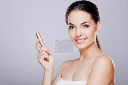 Foto de Retrato de niña con maquillaje nude perfecto en belleza. rimel de explotación del modelo de belleza. Mirando a cámara y sonriendo, se volvió un poco a un lado. Salón de belleza. Cabeza y los hombros - Imagen libre de derechos