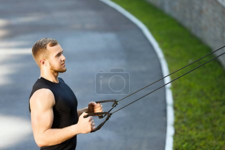 Muscular man pulling expander