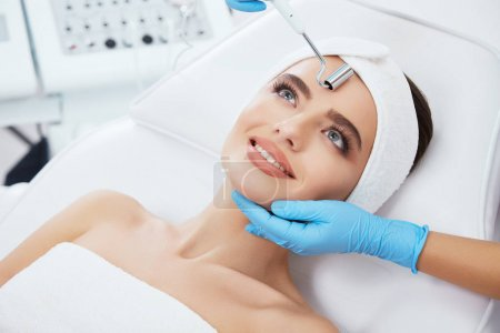 Beautiful young woman during cosmetic procedure