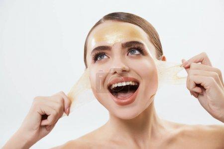 Photo pour Belle jeune femme avec masque jaune sur le visage. Femme arrachant masque - image libre de droit