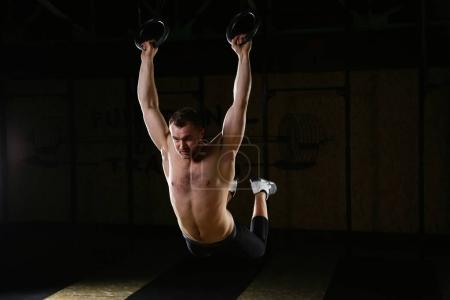 Man exercises with gymnastic rings