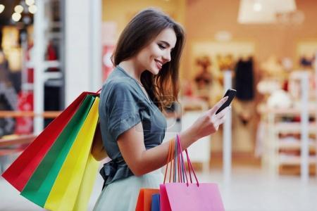 Photo pour Belle jeune femme avec sacs à provisions colorés et smartphone moderne, concept de shopping - image libre de droit