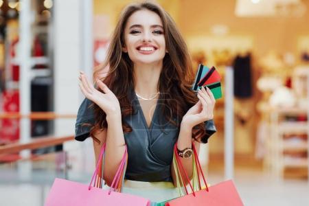 Photo pour Belle jeune femme debout avec des sacs à provisions colorés et des cartes de crédit, concept de shopping - image libre de droit