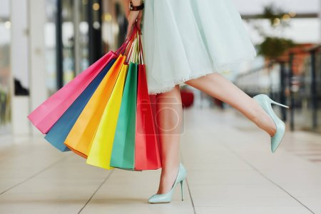 Photo for Female legs wearing light dress and hills standing with colorful shopping bags in shopping mall, shopping concept - Royalty Free Image