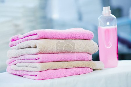 Rose detergent and heap of towels