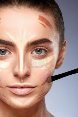 Photo pour Concept beauté. Portrait rapproché de femme avec contour sur le visage, maquillage. Types de maquillage de dessin, femme avec maquillage nu regardant la caméra - image libre de droit