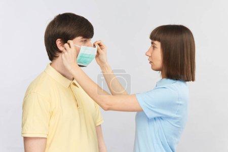 Photo pour Jeune femme portant un masque de protection stérile homme, comment mettre un masque de protection pendant une pandémie de coronavirus - image libre de droit