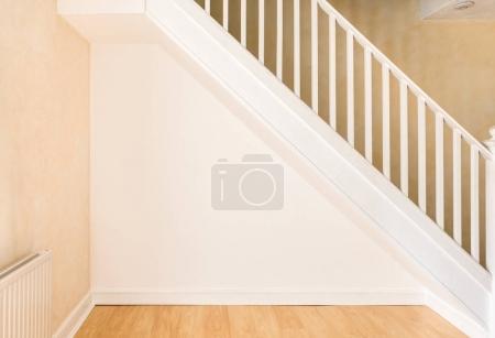 Photo pour Mur nouvellement décoré sous un escalier dans une pièce domestique après avoir été plâtré, peint et plinthes installées . - image libre de droit