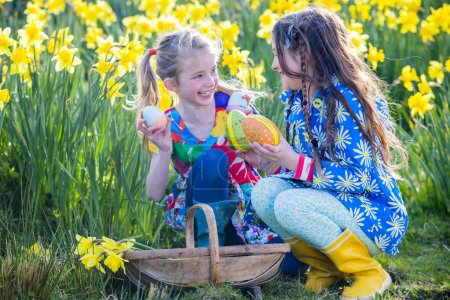 Photo for Two little girls are in a daffodil field looking for easter eggs together during an easter egg hunt. They have a basket with them and are holding some of the eggs with pride. - Royalty Free Image