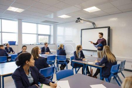 Photo pour Professeur masculin enseigne un groupe d'adolescents dans une leçon de lycée . - image libre de droit