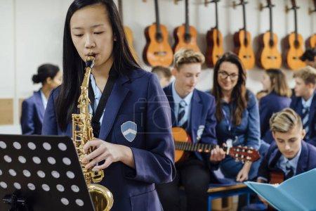 Photo pour Une adolescente joue du saxophone dans sa leçon de musique à l'école. Le reste de la classe est en arrière-plan, hors foyer . - image libre de droit