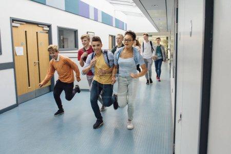 Photo pour Des élèves adolescents courent dans le couloir de leur école, pressés de partir pour les vacances d'été . - image libre de droit