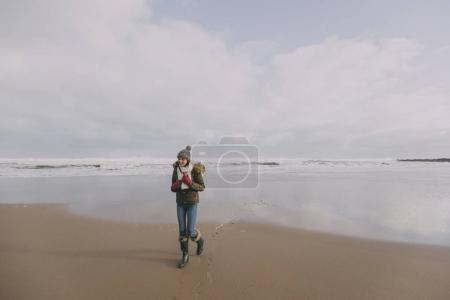 Young Woman Walking Along Winter Beach