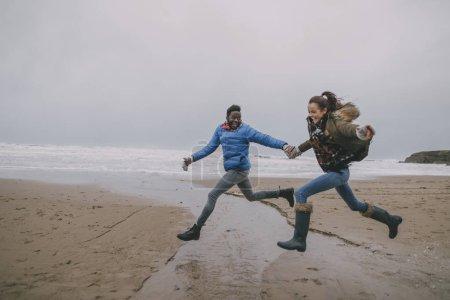 Foto de Una joven pareja salto juntos a lo largo de una playa en invierno. - Imagen libre de derechos