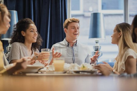 Photo for Coworkers are enjoying breakfast together in a restaurant before going to work. - Royalty Free Image
