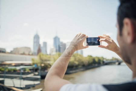 Photo for Millennial tourist is using his smart phone to take photos of the cityscape from a bridge in Melbourne, Victoria. - Royalty Free Image