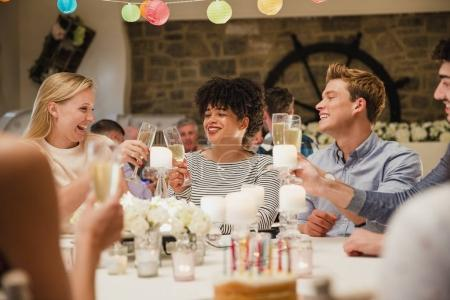 Photo for Friends are toasting glasses between themselves at their table at a birthday party. - Royalty Free Image