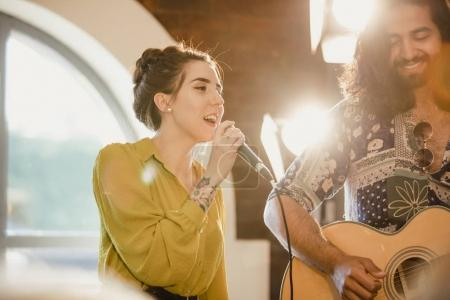 Photo for Musical performers at an event. There is a female singer and a male guitarist. - Royalty Free Image
