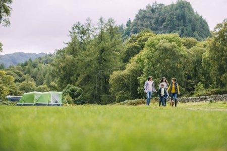 Photo pour Trois génération famille ont quitté leur tente d'aller pour une randonnée avec leur chien de compagnie. Il y a une grand-mère, une mère et ses deux enfants. - image libre de droit