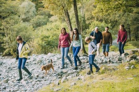 Photo for Three generation family are hiking together through the Lake District with their pet dog. - Royalty Free Image