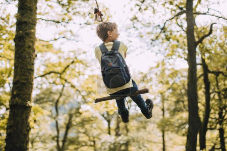 Photo for Little boy is having a go on a rope swing he has found while hiking. - Royalty Free Image
